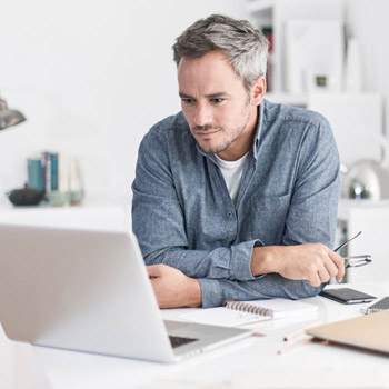 a man evaluating on laptop