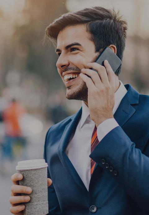 Man in business suit holding phone and drinking coffee