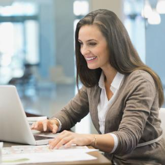 woman happily working behind her laptop