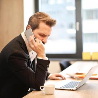 man on phone hiring remotely
